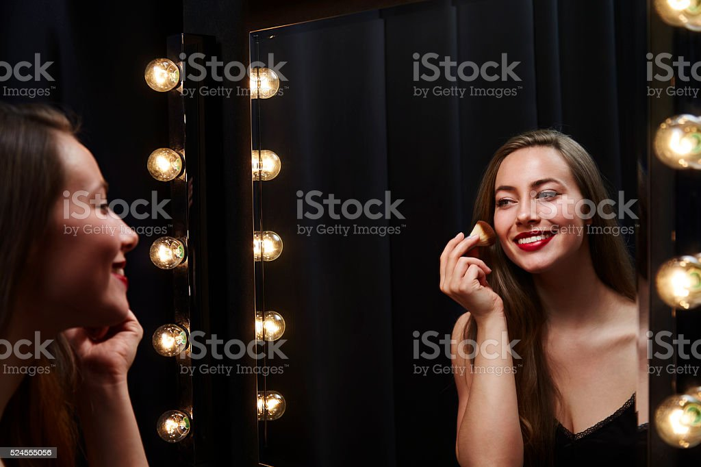 Young beautiful woman applying make up in mirror stock photo