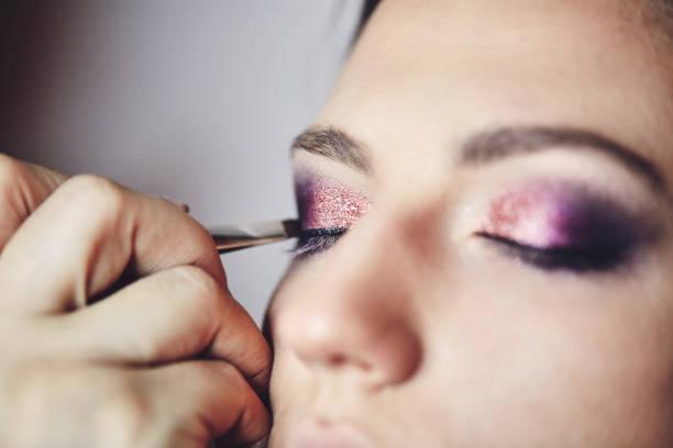 Young beautiful woman applying make-up by make-up artist. Process of making makeup. stock photo
