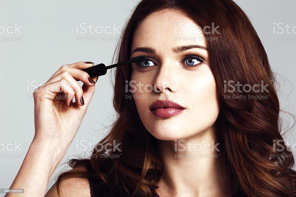 Young beautiful woman applying mascara makeup stock photo