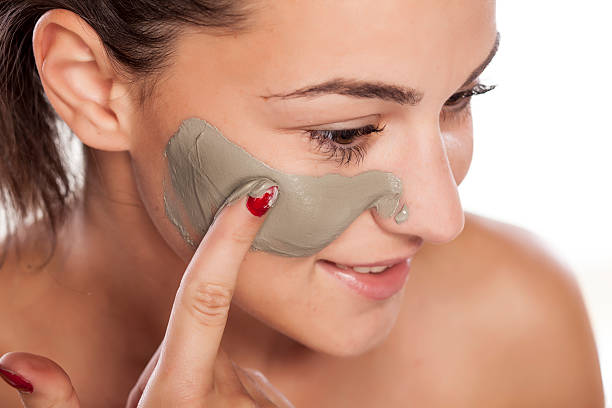 Young beautiful woman applying mask on her face stock photo