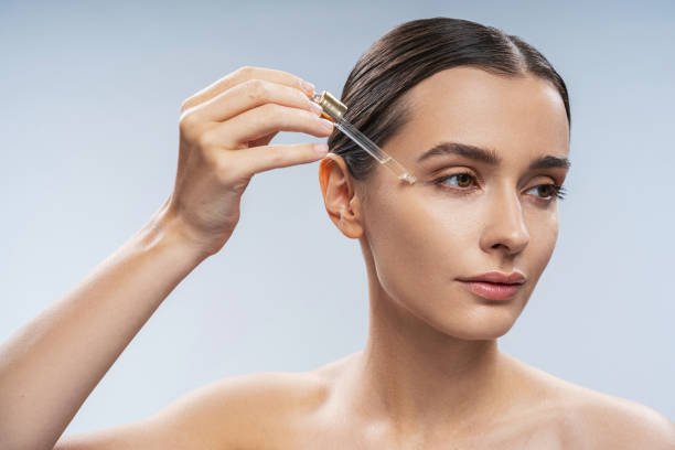 Young beautiful woman applying nature oil under eyes stock photo