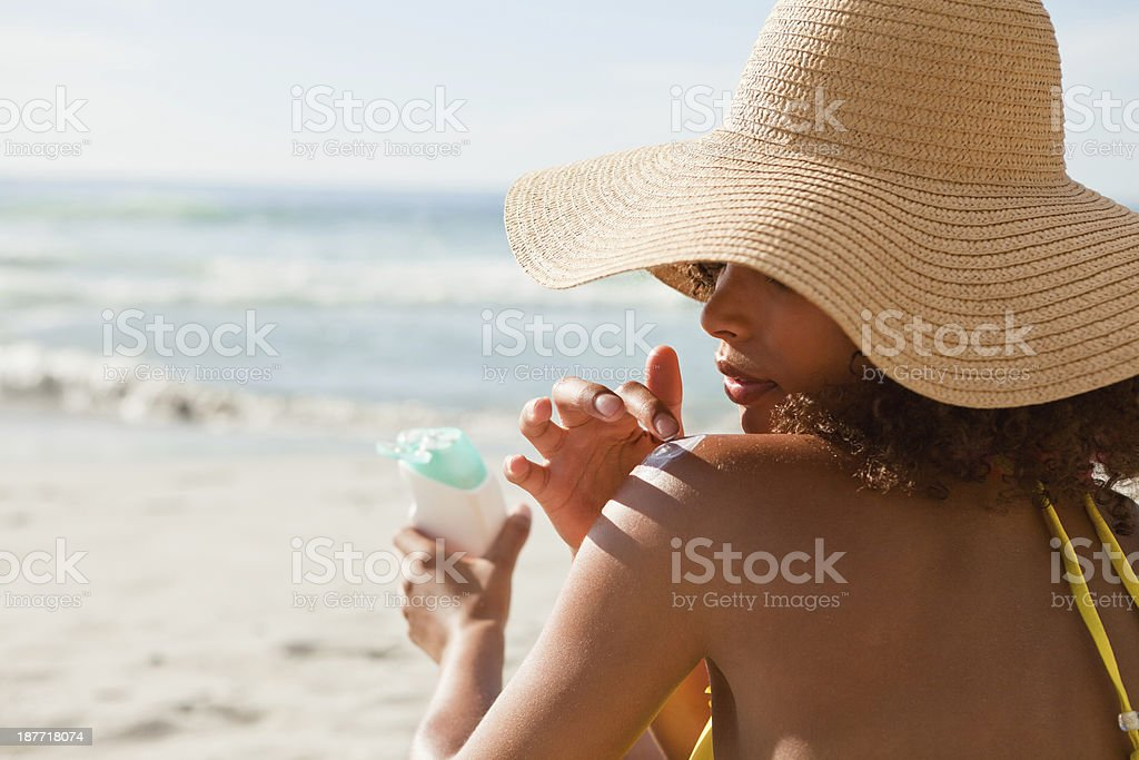 Young beautiful woman applying sunscreen on her shoulder stock photo