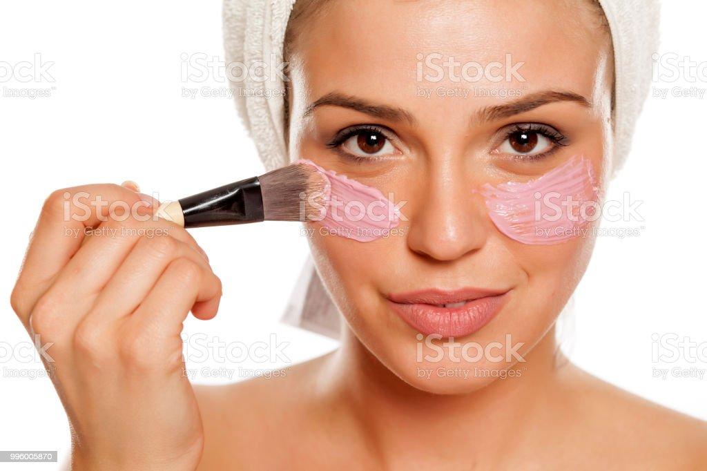 Junge schöne Frau Applyong Gesichts Maske auf ihr Gesicht mit einem Handtuch auf dem Kopf – Foto