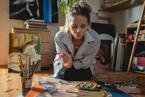 Junge schöne Frau im Inneren mit Pinsel arbeitet auf gezeichnetem Bild. Kunstkonzept des netten Künstlers in der Kunstschule oder zu Hause zwischen Bildern und Easels – Foto
