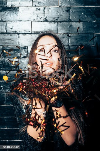 627933752istockphoto Young beautiful woman blowing сonfetti on party event 884833342