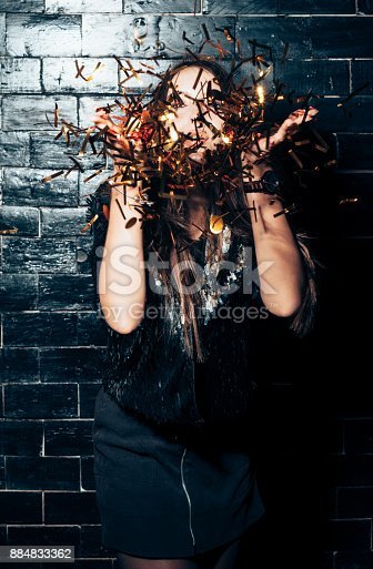 627933752istockphoto Young beautiful woman blowing сonfetti on party event 884833362