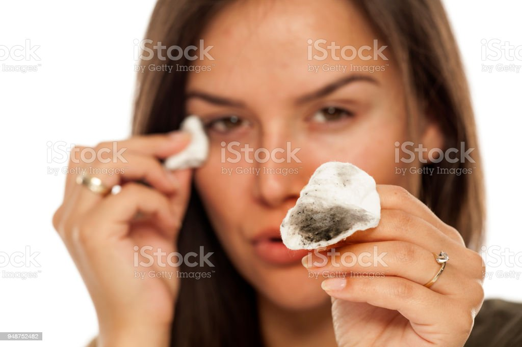 Young beautiful woman celaning her face with cotton pads on white background  - Stock image . e83f621f3
