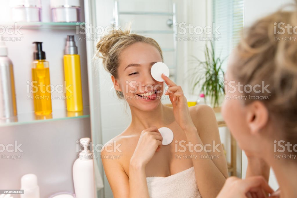 Young beautiful woman cleaning her face skin with cotton pad stock photo