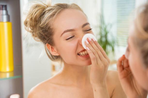 若くてきれいな女性綿パッドと彼女の顔の皮膚を洗浄 ストックフォト