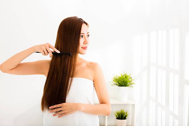 jeune belle femme ses cheveux peignage dans salle de séjour - peigne photos et images de collection