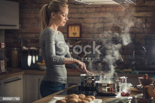 Young woman standing in the kitchen and cooking soup for lunch.