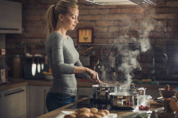 young beautiful woman cooking lunch in the kitchen. - woman cooking stock pictures, royalty-free photos & images