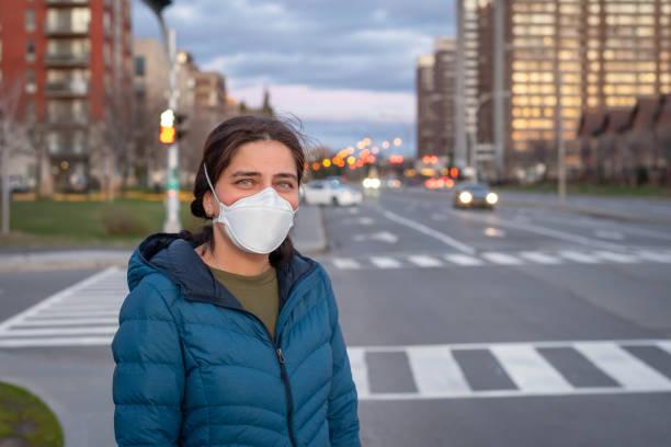 Young beautiful woman crossing city street wearing mask during coronavirus covid-19 pandemic stock photo