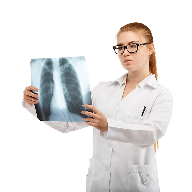 Young beautiful woman doctor inspects an X-ray of the chest stock photo