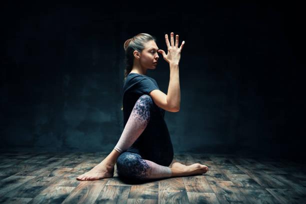 Junge schöne Frau tun Yoga asana Halb Herr der Fische posieren auf dunklen Raum – Foto