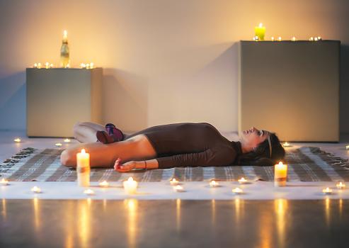 young beautiful woman doing yoga asana sleeping supine
