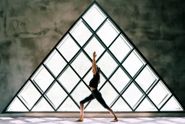 Junge schöne Frau tun Yoga Asana Krieger ich Pose auf großen dreieckigen Fenster Hintergrund – Foto
