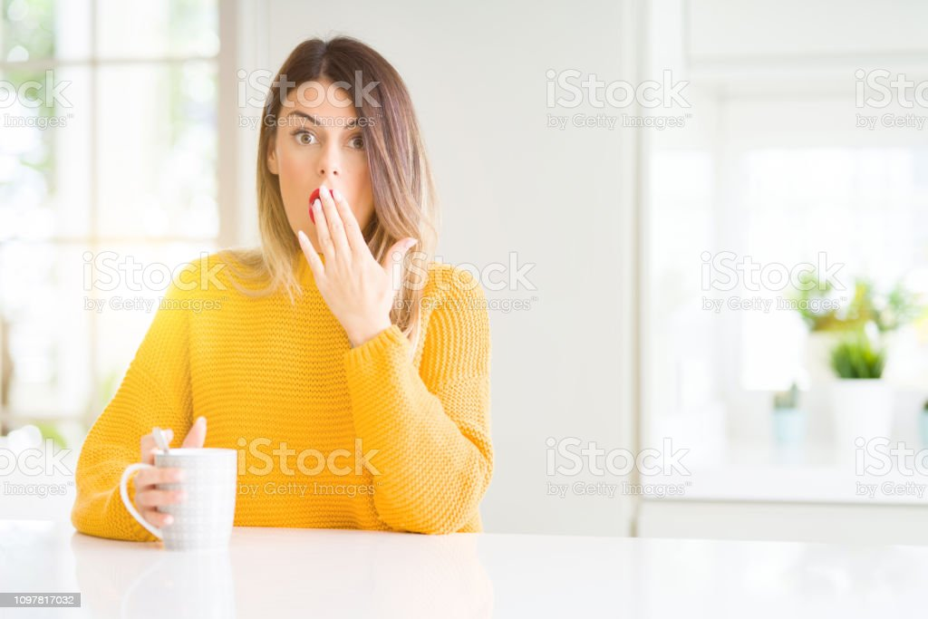 Young beautiful woman drinking a cup of coffee at home cover mouth...