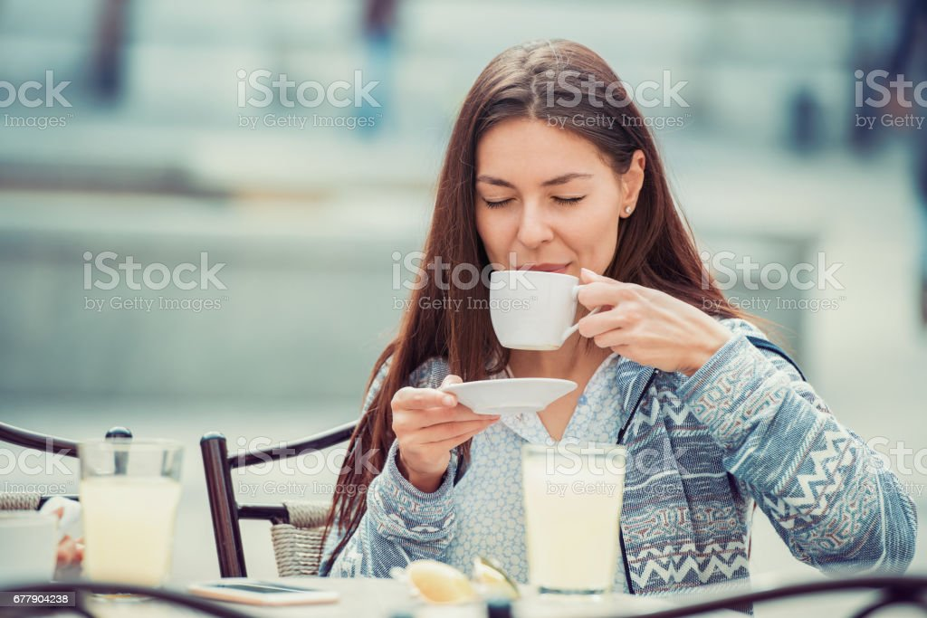 Young beautiful woman drinking coffee at cafe royalty-free stock photo
