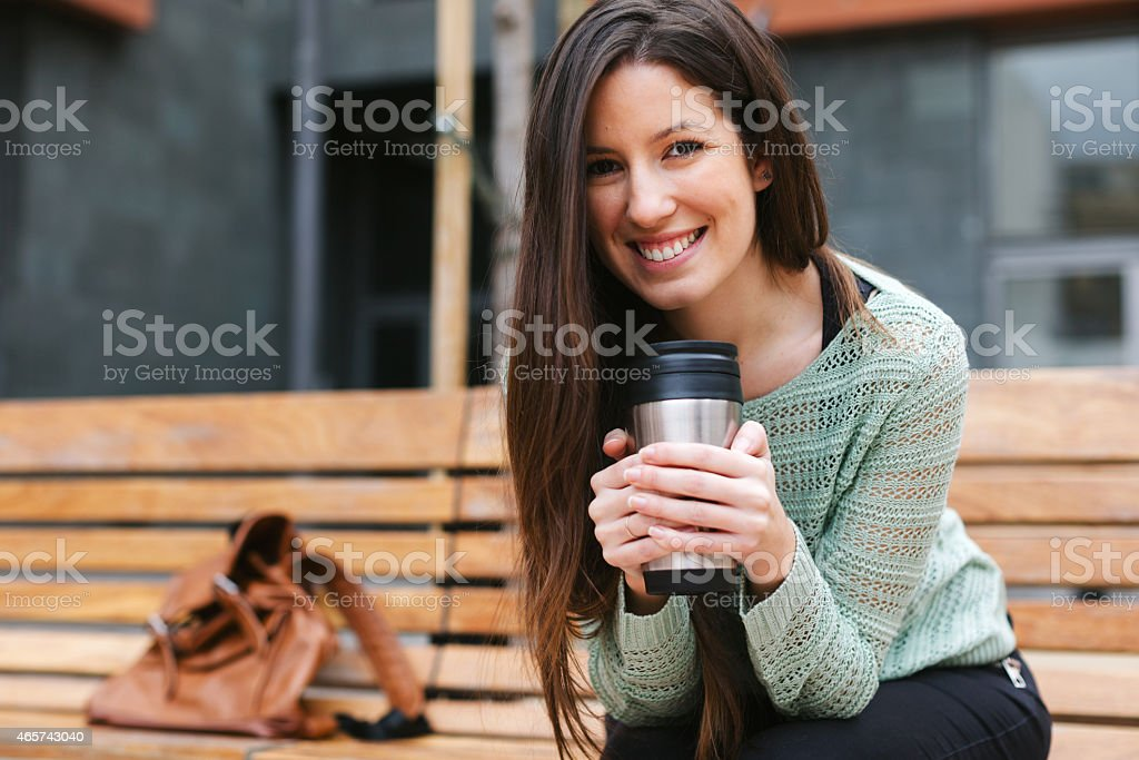 Young beautiful woman drinking coffee in outdoors. stock photo
