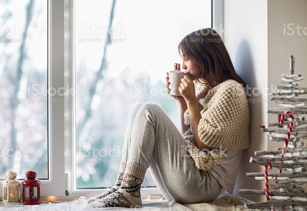 Young beautiful woman drinking hot coffee sitting on window sill – Foto