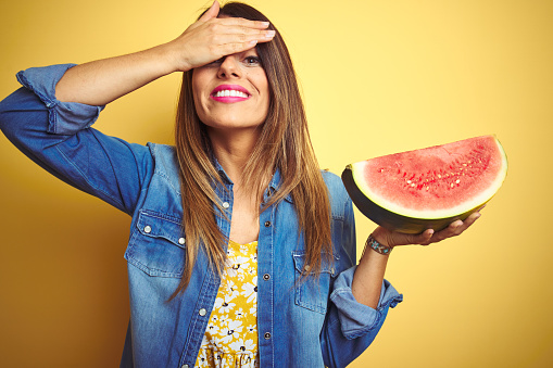 Young beautiful woman eating fresh healthy watermelon slice over yellow background stressed with hand on head, shocked with shame and surprise face, angry and frustrated. Fear and upset for mistake.
