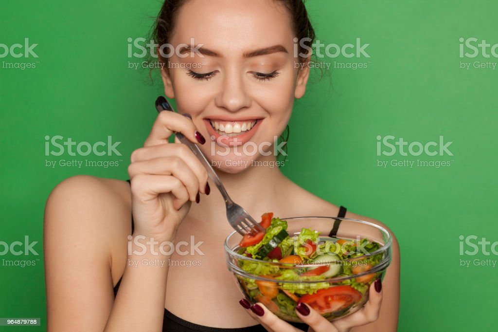 Young beautiful woman eating salad on green background royalty-free stock photo
