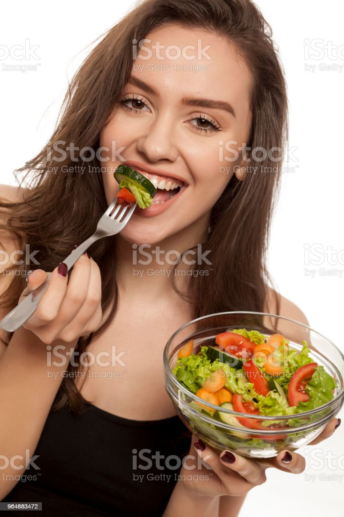 Young beautiful woman eating salad on white background royalty-free stock photo