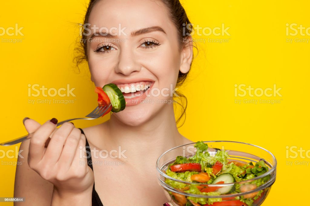 Young beautiful woman eating salad on yellow background stock photo