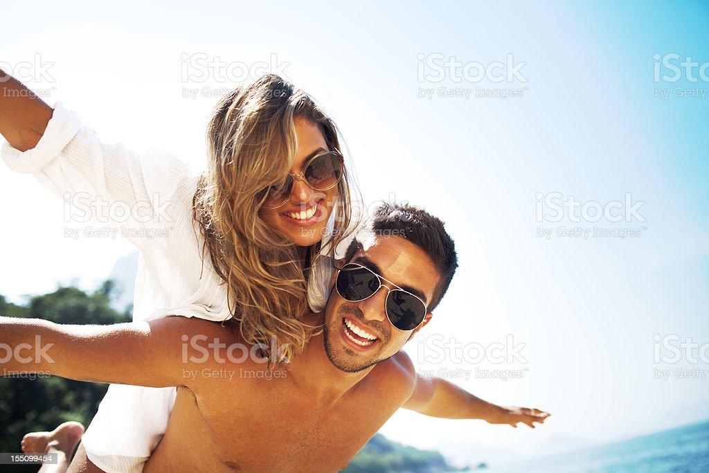 Young beautiful woman enjoys piggyback ride at the beach. stock photo