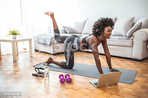 Young beautiful woman exercising at home, fitness concept. Young black woman sitting on the floor at home stretching. Young healthy beautiful woman in sportive top and leggings practicing yoga at home