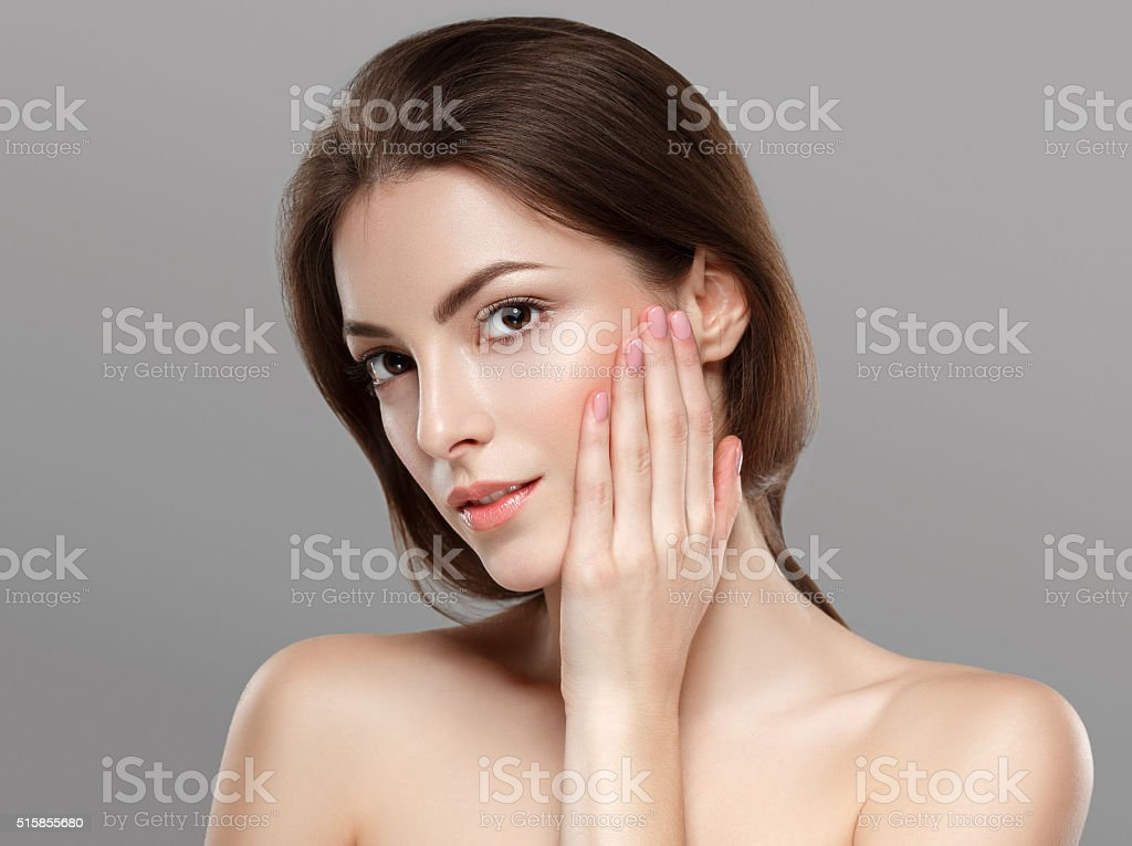 Young beautiful woman face portrait on gray background stock photo