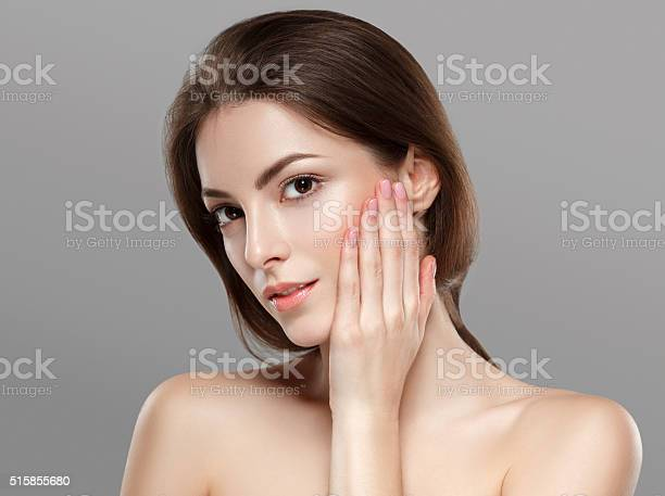 Young beautiful woman face portrait with healthy skin on gray background. Studio shot.