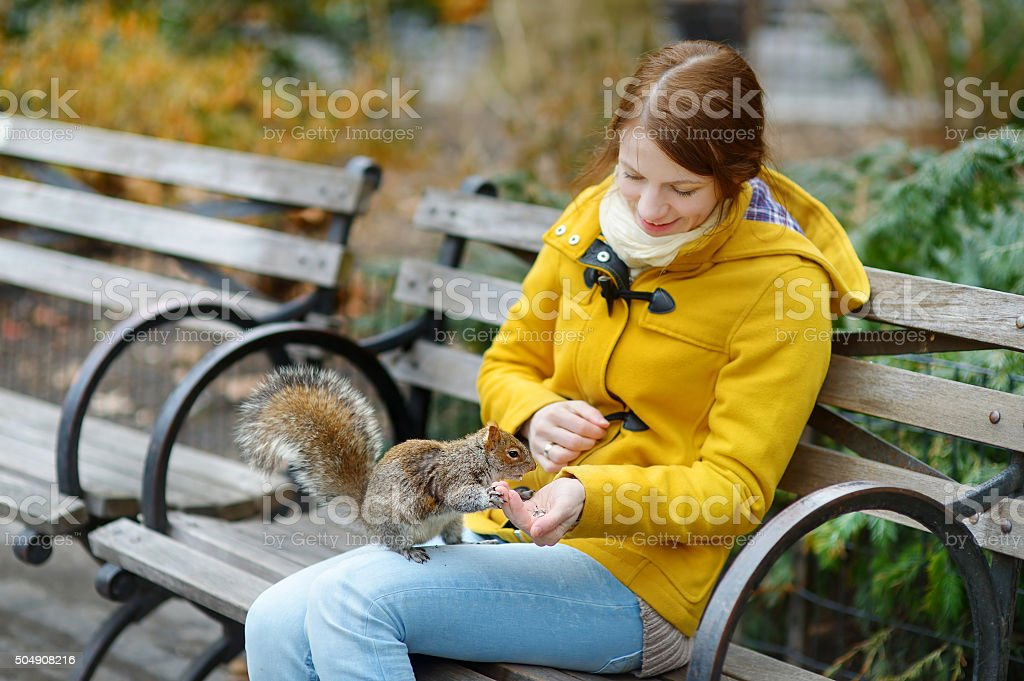 Young beautiful woman feeding a squirrel stock photo