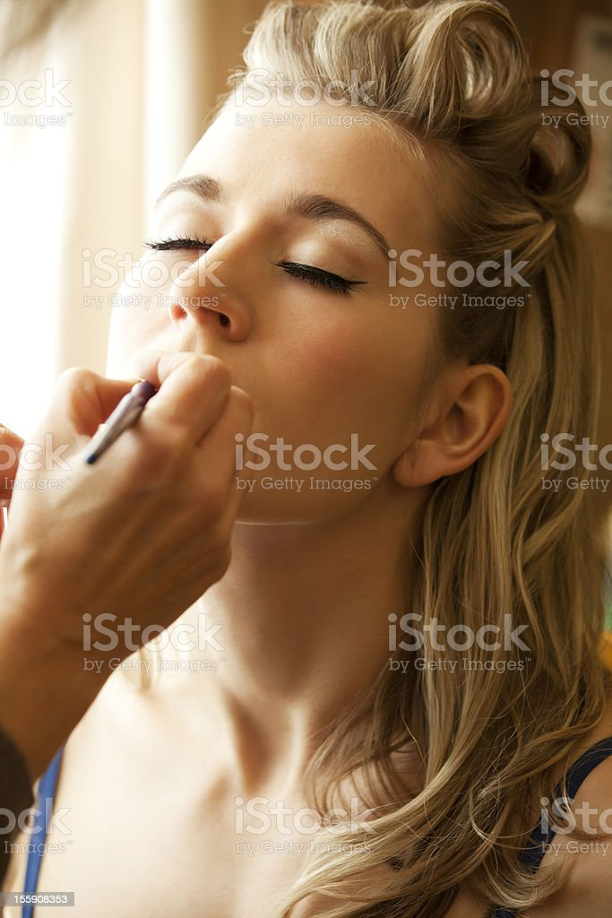 Young beautiful woman getting her makeup applied by MUA royalty-free stock photo