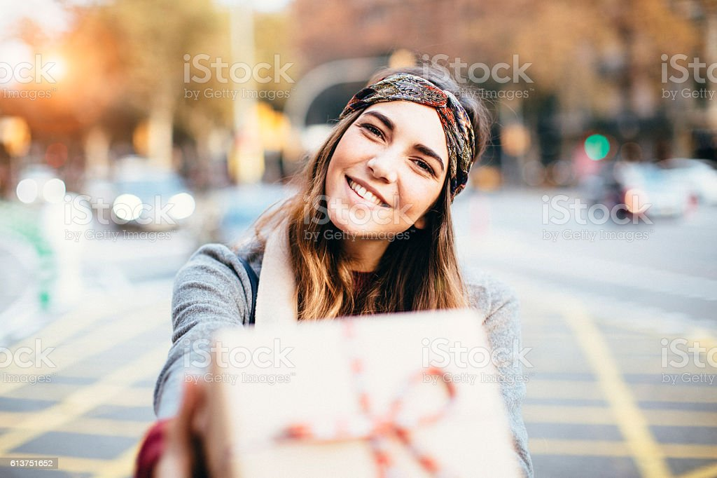 Young beautiful woman handing a present. stock photo