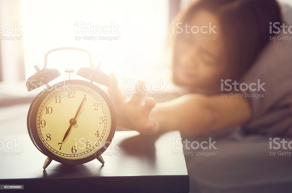 Young beautiful woman hates waking up early in the morning stock photo