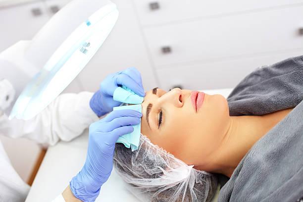 Young beautiful woman having facial beauty treatment stock photo