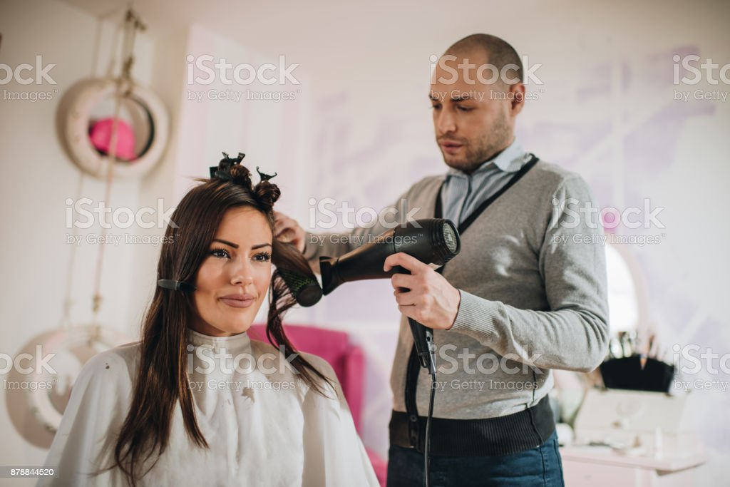 Young beautiful woman having her hair dried at hair salon. stock photo