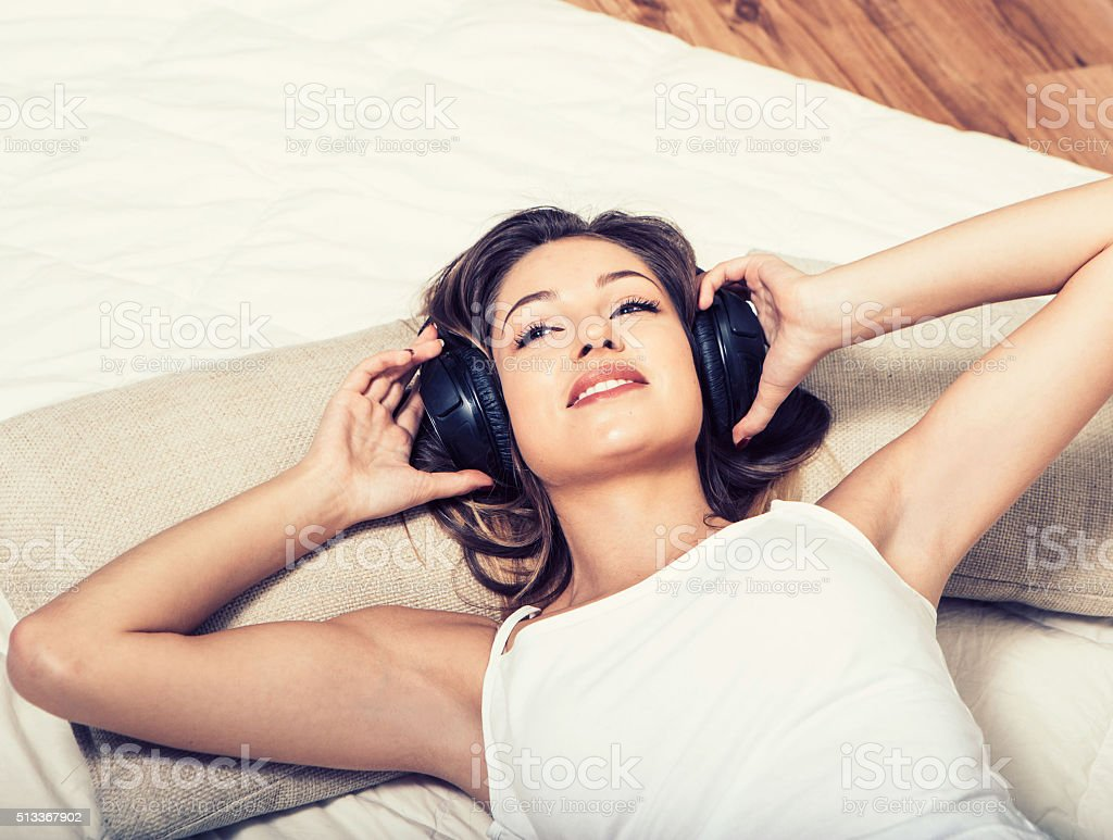 Young beautiful woman headphones listening music on bed stock photo