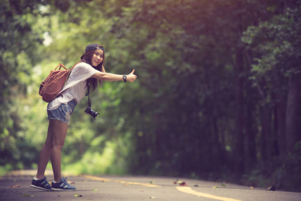 Young beautiful woman hitchhiking standing on road. stock photo