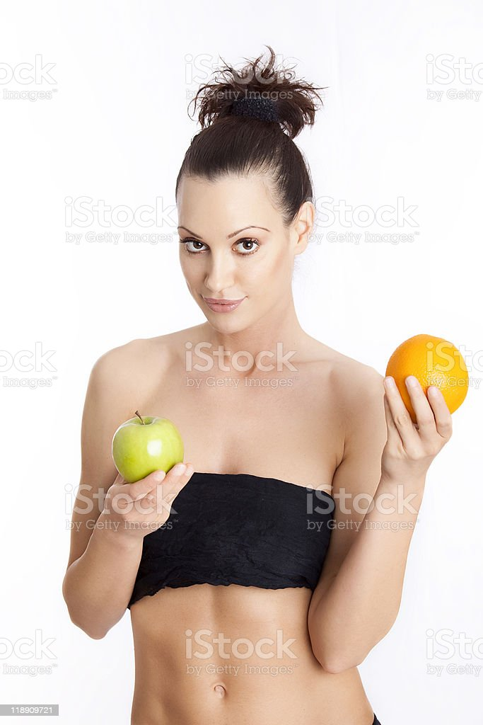 Young beautiful woman holding a green apple and orange royalty-free stock photo