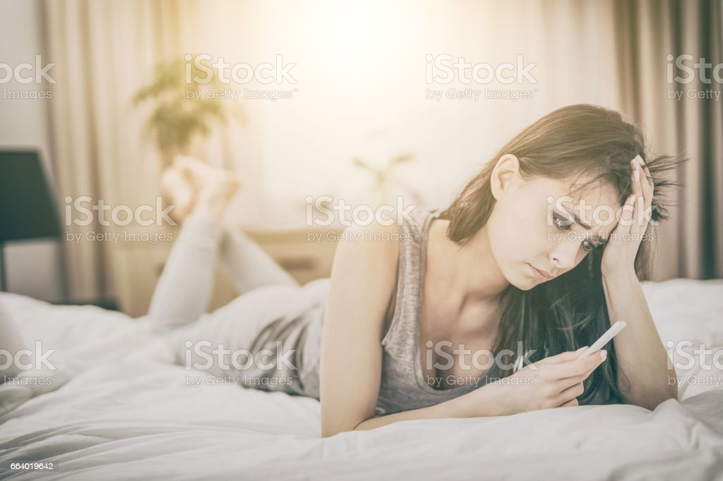 Young beautiful woman holding a pregnancy test. stock photo