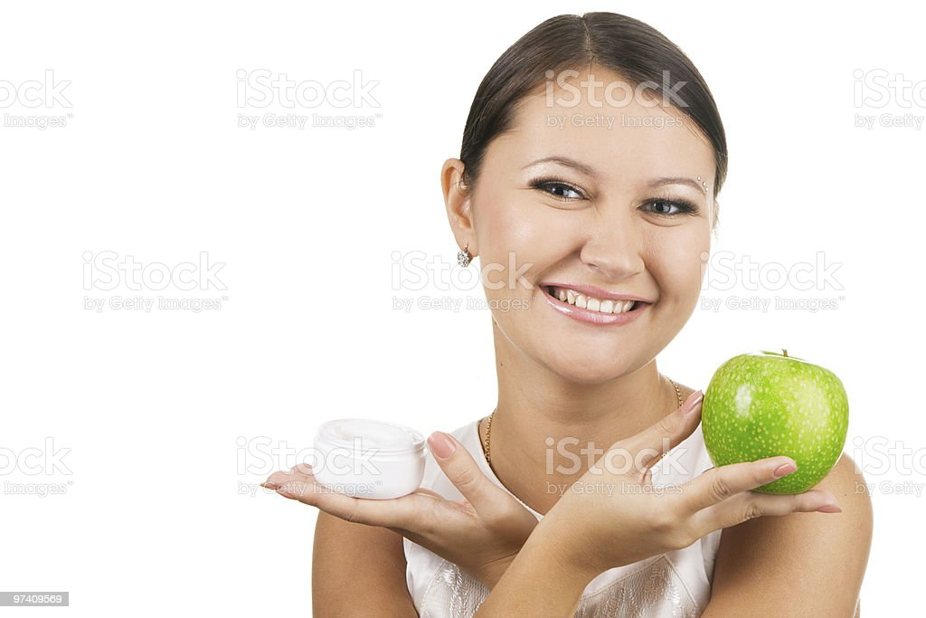 Young beautiful woman holding an apple and skin cream royalty-free stock photo