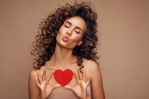 Young beautiful woman holding artificial heart