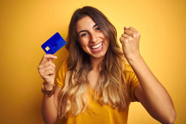 młoda piękna kobieta trzymająca kartę kredytową na żółtym odizolowanym tle krzycząc dumna i świętująca zwycięstwo i sukces bardzo podekscytowana, dopingująca emocje - credit card zdjęcia i obrazy z banku zdjęć