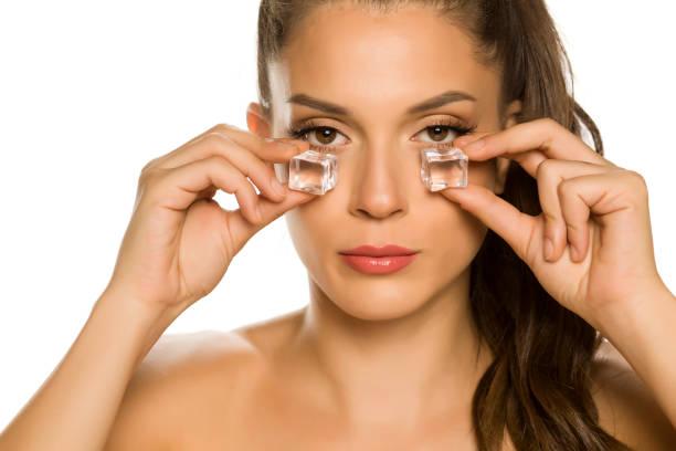 年輕的美麗女人拿著冰塊的眼睛在白色背景圖像檔
