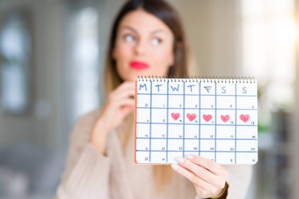 young beautiful woman holding menstruation calendar at home serious face thinking about question, very confused idea - mestruazione foto e immagini stock