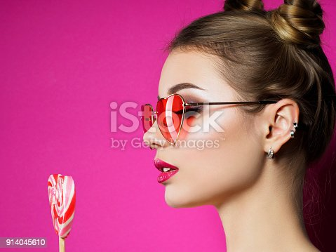 istock Young beautiful woman holds heart shaped lollipop 914045610