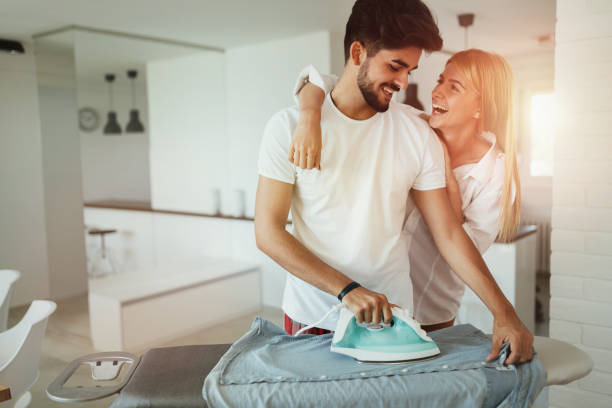 young beautiful woman hugging her attractive boyfriend - ironing stock photos and pictures